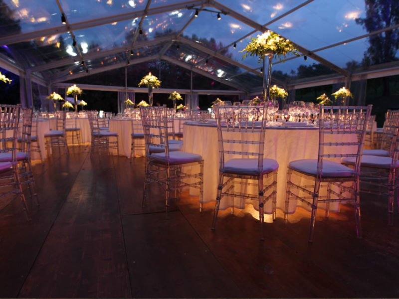Visione notturna di tavoli con luce e sedie chiavarine trasparenti